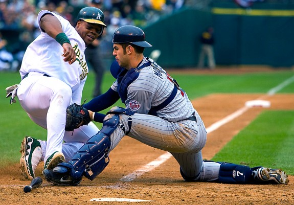 Oakland Athletics base runner Frank Thomas is tagged out at home plate by Minnesota Twins catcher Joe Mauer during Game 3 of the Amercian League Division Series at the Oakland Coliseum in Oakland, California on October 6, 2006. (Photo by Brad Mangin)