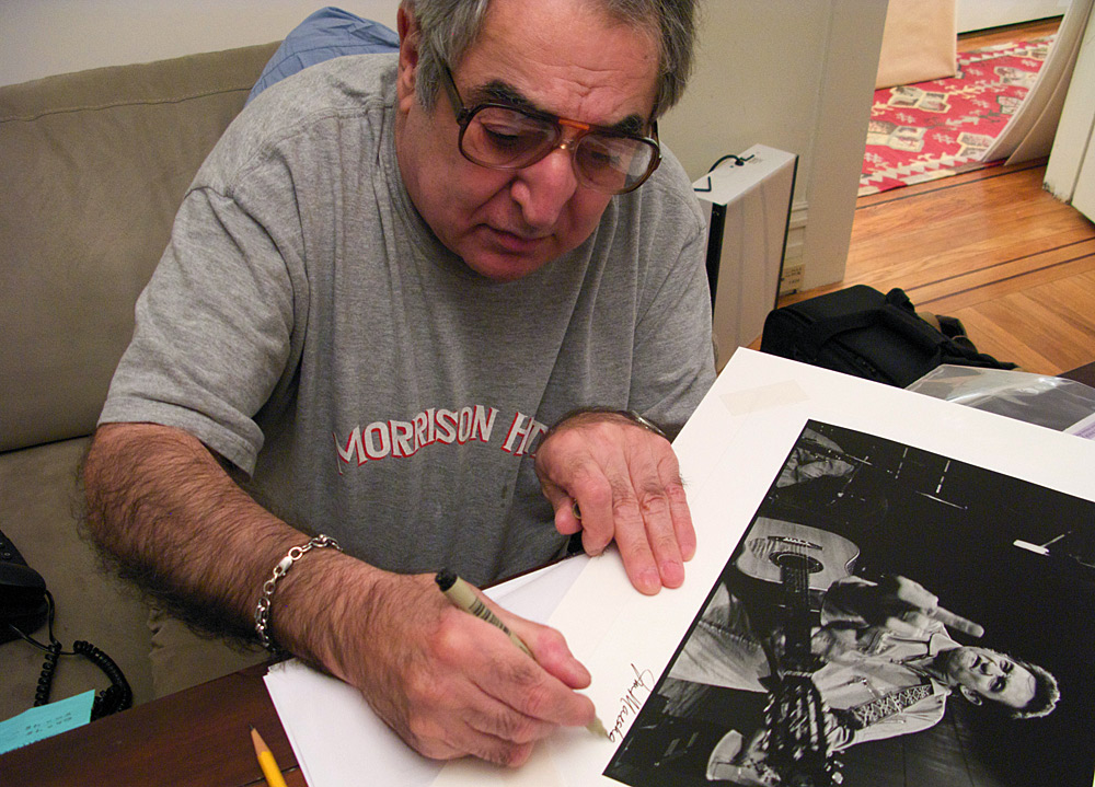 Jim Marshall signs his iconic Johnny Cash print for Brad Mangin in his San Francisco home on Feruary 11, 2009. (Photo by Grover Sanschagrin)