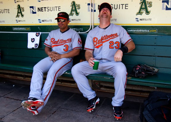 Cesar Izturis (left) and Ty Wigginton of the Baltimore Orioles get ready in the dugout before the game between the Baltimore Orioles and the Oakland Athletics on Saturday, April 17, 2010, at the Oakland Coliseum in Oakland, California. The Athletics defeated the Orioles 4-3. (Photo by Brad Mangin/MLB Photos)