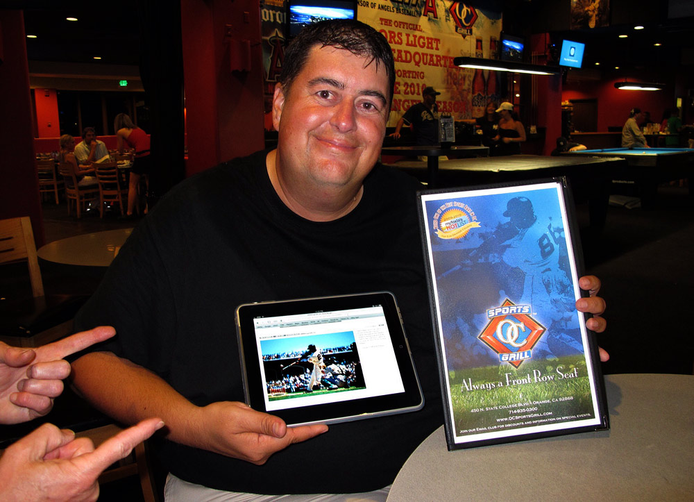 Brad Mangin shows off the menu from the OC Sports Grill with his photograph of Barry Bonds featured on the cover, along with the same image in his online archive on the screen of Dan MacMedan's iPad. (Photo by Dan MacMedan)