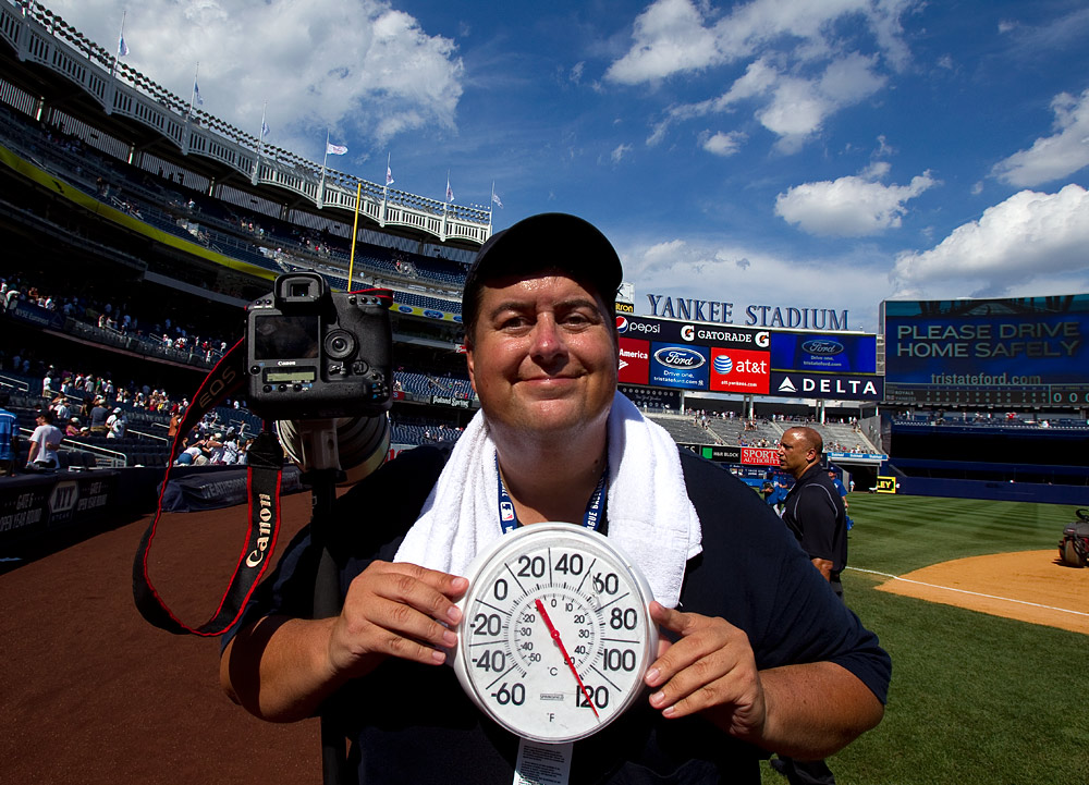 Photographer Brad Mangin stands on the field holding a thermometer reading 120 degrees on the field after the game between the Kansas City Royals and the New York Yankees  at Yankee Stadium on July 24, 2010 in the Bronx borough of New York City. (Photo by Tomasso DeRosa)