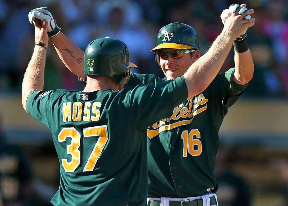 Josh Reddick #16 of the Oakland Athletics celebrates with teammate Brandon Moss #37 at home plate after hitting a two-run home run in the bottom of the 8th inning against the Seattle Mariners during the game at O.co Coliseum on Sunday, September 30, 2012 in Oakland, California. (Photo by Brad Mangin)