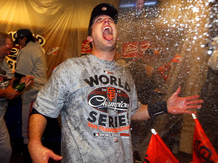 Buster Posey of the San Francisco Giants celebrates in the clubhouse after the Giants defeat the Detroit Tigers to win the 2012 World Series on Sunday, October 28, 2012 at Comerica Park in Detroit, Michigan. (Photo by Brad Mangin/MLB Photos)