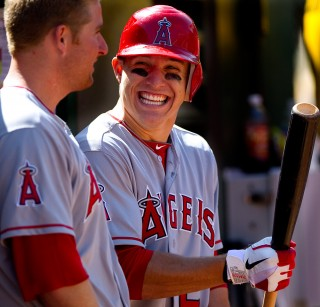 Mike Trout #27 (right) and Mark Trumbo #44 of the Los Angeles Angels talk in the dugout during the game against the Oakland Athletics at the Oakland Coliseum on Wednesday May 23, 2012 in Oakland, California. (Photo by Brad Mangin)