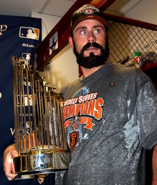 Brian Wilson of the San Francisco Giants holds up the World Series trophy after their 3-1 victory to win the World Series over the Texas Rangers in Game Five of the 2010 World Series at Rangers Ballpark on Monday, November 1, 2010 in Arlington, Texas. (Photo by Brad Mangin/MLB Photos)