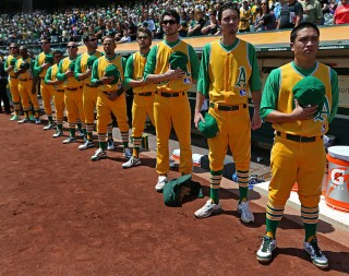 Bat boy Austin Ginn of the Oakland Athletics stands in front of the team during the National Anthem before the game against the Los Angeles Angels during the game at O.co Coliseum on 1969 Turn Back the Clock Day on Saturday, July 27, 2013 in Oakland, California. (Photo by Brad Mangin)