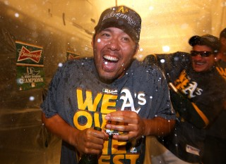 Kurt Suzuki #22 and Jarrod Parker #11 of the Oakland Athletics celebrate with champagne in the clubhouse after the A's defeated the Minnesota Twins 11-7 to clinch the American League Western Division title at O.co Coliseum on Sunday, September 22, 2013 in Oakland, California. (Photo by Brad Mangin)