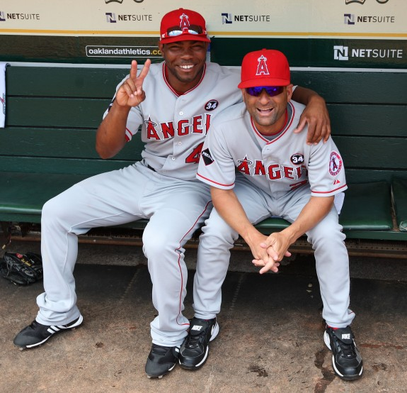 Howard Kendrick #47 (left) and coach Dino Ebel #21 of the Los Angeles Angels of Anaheim get ready in the dugout before the game against the Oakland Athletics at the Oakland-Alameda County Coliseum on July 18, 2009 in Oakland, California.